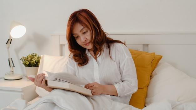 アジアの年配の女性は家でくつろいでいます。アジアのシニア中国女性は夜のコンセプトで自宅の寝室のベッドに横たわっている間本を読んで休憩時間をお楽しみください。 無料写真
