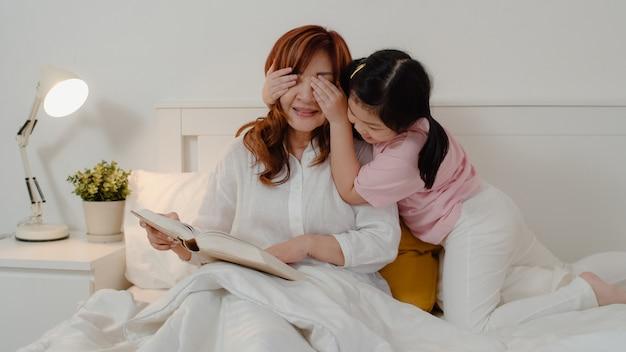Азиатская бабушка отдыхает дома. старший китаец, бабушка счастливая ослабляет с молодой девушкой внучки наслаждается близким ее сюрпризом глаз играя совместно лежать на кровати в спальне дома на концепции ночи. Бесплатные Фотографии