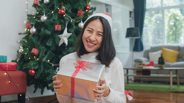 Азиатские женщины празднуют рождественский праздник. женский подросток носить свитер и шляпу рождество расслабиться счастливый подарок, улыбаясь возле елки наслаждаться рождественские зимние каникулы вместе в гостиной дома. Бесплатные Фотографии