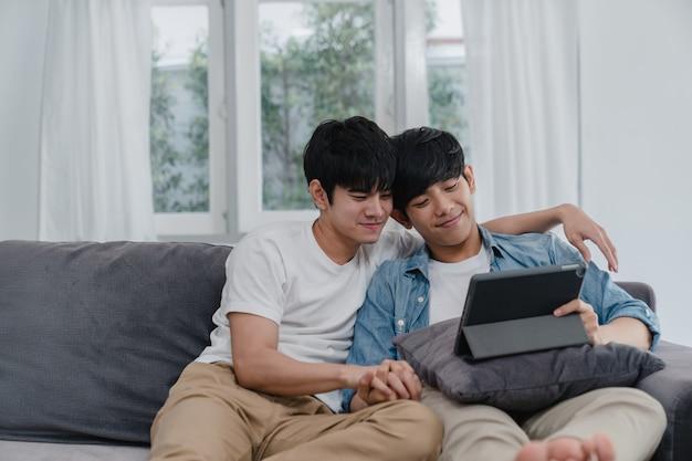 Молодые пары гомосексуалиста используя таблетку дома. азиатки-лгбтк + мужчины с удовольствием отдыхают, используя технологии, смотря фильмы в интернете вместе, лежа на диване в гостиной. Бесплатные Фотографии