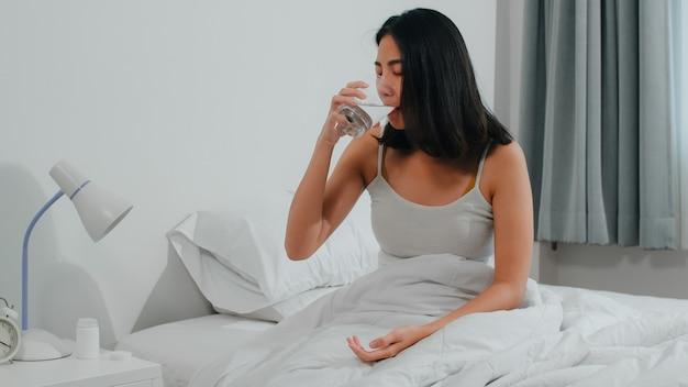 不健康な病気のインドの女性は不眠症に苦しんでいます。アジアの若い女性が鎮痛剤を服用して頭痛の痛みを和らげ、朝は自宅の寝室のベッドの上に座って水を飲みます。 無料写真