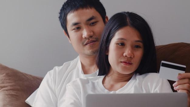 若いアジアの妊娠カップルの自宅でのオンラインショッピング。ママとパパは、自宅のリビングルームのソファに横たわっている間、ラップトップテクノロジーとベビー用品を購入するクレジットカードを使用して幸せを感じています。 無料写真