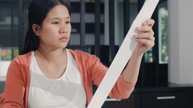 若いアジア妊婦の自宅での収入と支出の記録。ママは心配し、深刻で、ストレスを記録しながら、自宅の居間で働く予算、税金、財務書類を記録します。 無料写真