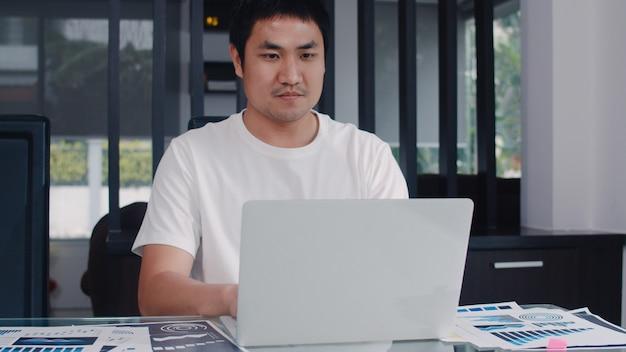 Молодые азиатские отчеты бизнесмена дохода и расходов дома. мужчина беспокоился, серьезный, стресс при использовании ноутбука, записи бюджета, налогов, финансовых документов, работающих в гостиной дома. Бесплатные Фотографии