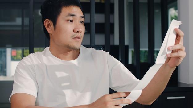 アジアの若いビジネスマンの自宅での収入と支出の記録。男性は、ラップトップの記録予算、税金、自宅の居間で働く財務書類を使用している間、心配して、深刻な、ストレスを感じます。 無料写真