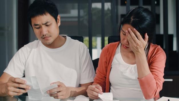 自宅での収入と支出の若いアジアの妊娠カップルの記録。ママは心配し、深刻で、ストレスを記録しながら、自宅の居間で働く予算、税金、財務書類を記録します。 無料写真