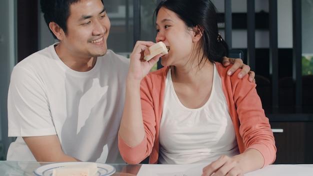 若いアジア妊婦腹に赤ちゃんを描画し、ノートブックで家族。自宅のリビングルームのテーブルで子供の世話をしながら、肯定的で平和な笑顔を幸せにしながら、彼の妻にサンドイッチを与えるお父さん。 無料写真