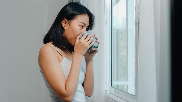 笑顔で寝室の窓の近くのコーヒーや紅茶のカップを飲んで幸せな美しいアジアの女性。若いラテンの女の子はカーテンを開けて、朝リラックスします。自宅でのライフスタイルの女性。 無料写真