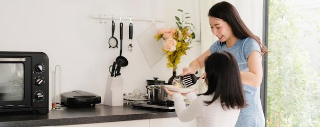 若いアジアの日本人ママと娘が自宅で料理します。朝は家のモダンなキッチンで朝食の食事のためにパスタとスパゲッティを一緒に作る幸せなライフスタイルの女性。 無料写真