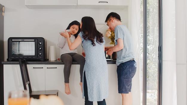 アジアの若い日本人家族が自宅で料理します。ライフスタイルハッピーママ、パパ、娘の朝の家でモダンなキッチンで朝食の食事のためにパスタとスパゲッティを一緒に作る。 無料写真