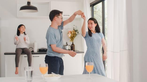 幸せな若いアジアの家族は、家で朝食をとった後、音楽とダンスを聴きます。魅力的な日本人の母父と子娘は、午前中にモダンなキッチンで一緒に時間を過ごしています。 無料写真