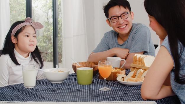 アジア系の日本人家族は家で朝食をとります。アジアのママ、パパ、娘は、朝、台所のテーブルの上のボウルでパン、コーンフレーク、シリアル、ミルクを食べながら一緒に話して幸せを感じています。 無料写真
