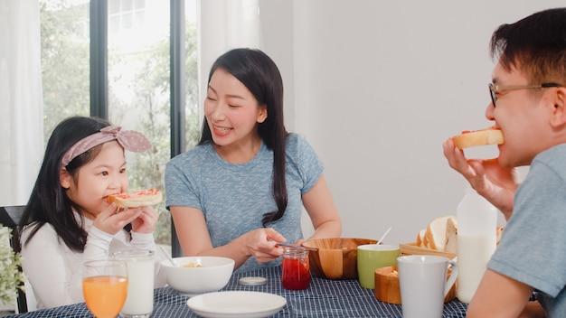 アジア系の日本人家族は家で朝食をとります。娘のパンにいちごジャムを作るアジアの幸せなお母さんは、朝は台所のテーブルの上のボウルにコーンフレークシリアルと牛乳を食べる。 無料写真