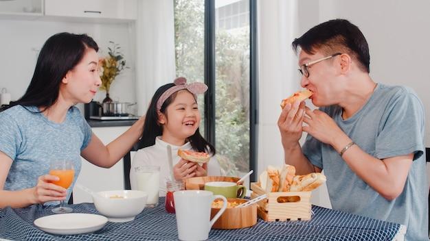 Азиатская японская семья завтракает дома. азиатские мама, папа и дочь, чувствуя себя счастливыми говорить вместе, пока едят хлеб, кукурузные хлопья, хлопья и молоко в миске на столе в кухне по утрам. Бесплатные Фотографии