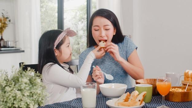 アジア系の日本人家族は家で朝食をとります。アジアの母と娘が一緒に幸せな話をしながらパンを食べて、オレンジジュース、コーンフレークシリアル、牛乳をモダンなキッチンのテーブルの上の朝に飲みます。 無料写真