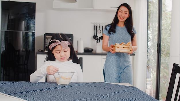 アジア系の日本人家族は家で朝食をとります。アジアのお母さんと娘は、朝の家でモダンなキッチンのテーブルの上のボウルにパン、コーンフレークシリアル、牛乳を食べながら一緒に話して幸せを感じます。 無料写真