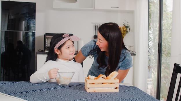 Азиатская японская семья завтракает дома. азиатские мама и дочь, чувствуя счастливый разговор вместе, пока едят хлеб, кукурузные хлопья зерновых и молоко в миску на столе в современной кухне дома утром. Бесплатные Фотографии