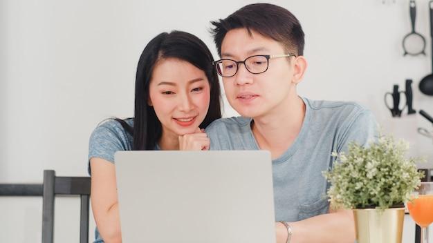 Молодые азиатские пары наслаждаются ходить по магазинам онлайн на компьтер-книжке дома. образ жизни молодой муж и жена счастливы купить электронной коммерции после того, как позавтракать в современной кухне дома утром. Бесплатные Фотографии