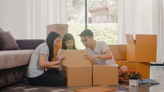 幸せなアジアの若い家族の移転除去は、新しい家に定住します。中国の両親と子供たちは、移動日にリビングルームで段ボール箱または小包を開梱します。不動産の住宅、ローン、住宅ローン。 無料写真