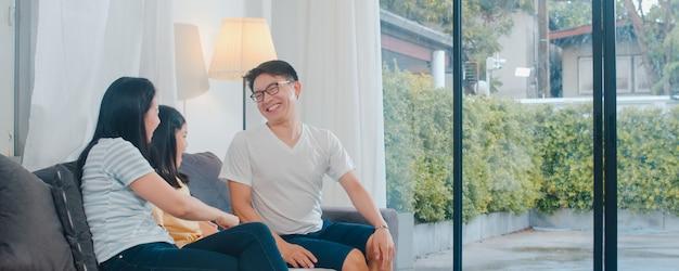 幸せな若いアジア家族が自宅のソファで一緒に遊ぶ。幸せを楽しんでいる中国の母父と子の娘は、夜にモダンなリビングルームで一緒に時間を過ごしてリラックスします。 無料写真