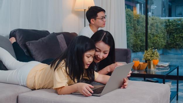 アジアの家族は、自由時間を楽しんで家で一緒にリラックスします。ラップトップを使用してライフスタイルのママと娘はインターネットで映画を見て、パパは現代の家のリビングルームでテレビを見ます。 無料写真