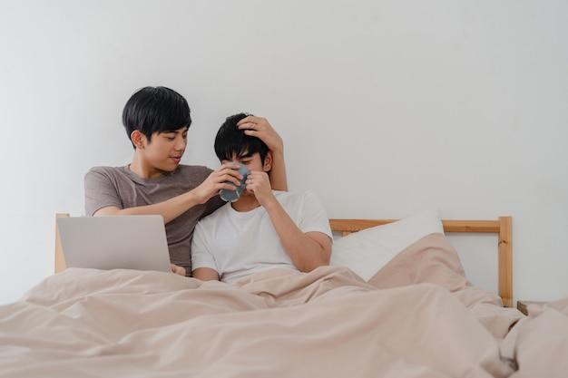 アジアのゲイの男性カップルは、コンピューターのラップトップを使用して、現代の家でコーヒーを飲みます。若いアジアの恋人男性幸せな目覚めた後、一緒に家で寝室のベッドに横になっている映画を見ながら一緒に残りをリラックスします。 無料写真