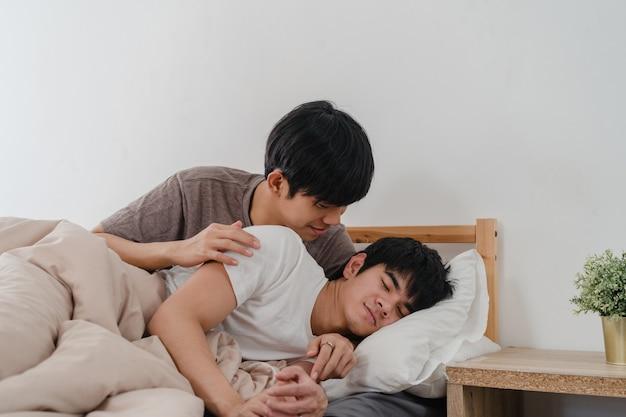 Азиатские пары геев целуют и обнимают на кровати дома. молодые азиатские лгбт-мужчины с удовольствием отдыхают вместе, проводят романтическое время после того, как просыпаются утром в спальне дома. Бесплатные Фотографии