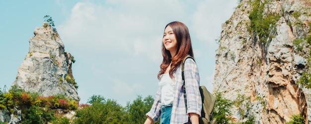 山の湖で歩いてバックパックで陽気な若い旅行者のアジアの女性。韓国の十代の少女は幸せな自由を感じて彼女の休暇の冒険をお楽しみください。ライフスタイルは旅行し、自由な時間の概念でリラックスします。 無料写真