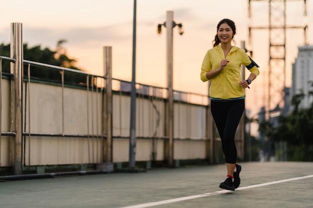 エクササイズを実行している美しい若いアジアアスリート女性は、都市環境でエクササイズします。早朝に歩道橋でスポーツ服を着ている日本人の十代の少女。都会でスポーティーに活躍するライフスタイル。 無料写真