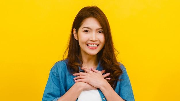 Портрет молодой азиатской леди с позитивным выражением, радостным и захватывающим, одетый в повседневную одежду и глядя на камеру через желтую стену. счастливая прелестная радостная женщина радуется успеху. Бесплатные Фотографии