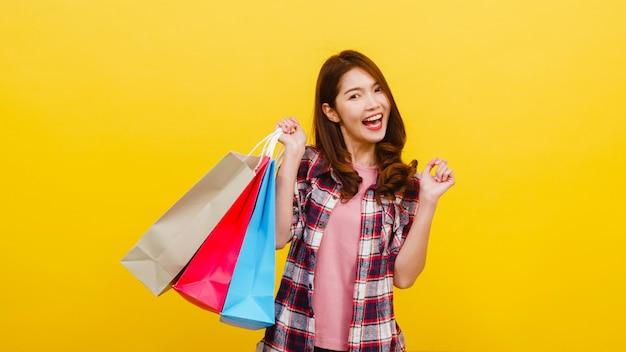 幸せな興奮してアジアの若い女性がカジュアルな服で立ち上がって黄色の壁を越えてカメラを見て手で買い物袋を運ぶします。顔の表情、季節限定セール、消費者のコンセプト。 無料写真