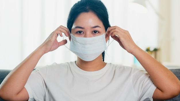 落ち込んでいるアジアビジネスの女性の社会的距離が家にいるとき、家のリビングルームのソファーに座っている防護マスクと自己検疫時間、中国でのパンデミック、コロナウイルスの概念。 無料写真