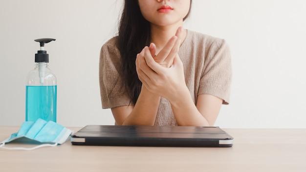 Азиатская женщина используя руки мытья дезинфицирующее средство геля спирта перед открытой таблеткой для защищает коронавирус. женщина пьет алкоголь, чтобы убрать для гигиены, когда социальное дистанцирование остается дома и сам карантин времени Бесплатные Фотографии