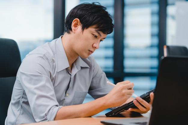 成功したエグゼクティブアジア青年実業家スマートカジュアルウェアの描画、書き込み、デジタルタブレットコンピューターでペンを使用して、現代のオフィスでインスピレーション検索アイデア作業プロセスを考えています。 無料写真