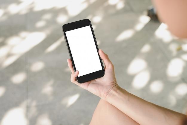 スマートフォンを使用している若いアジア人の女性は、カフェで白い空白の画面をモックします 無料写真
