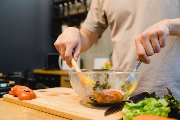 幸せな美しいアジア人は台所でサラダの食べ物を準備する 無料写真