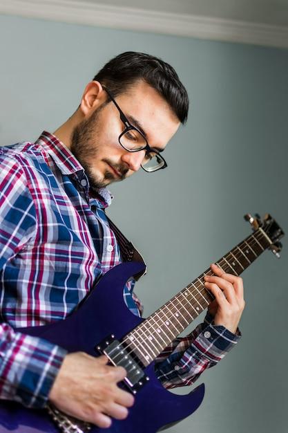 男は自宅でエレキギターを弾くことを学ぶ Premium写真