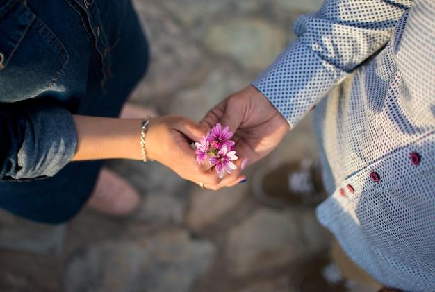 夕暮れ時の花とカップルの手 Premium写真