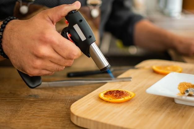 バーテンダーはカクテルを準備するためのバーでガストーチでオレンジを燃やす Premium写真