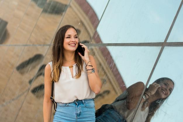 若い女性は彼女のスマートフォンを使用しています、彼女の後ろに鏡があります Premium写真