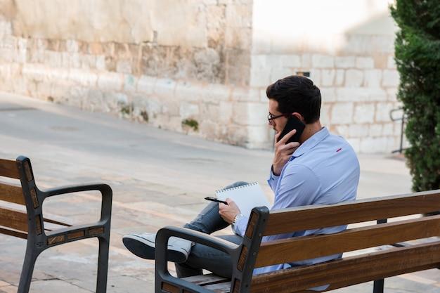 彼は携帯電話で話している間、青年実業家はベンチに座って、彼のノートに書いています Premium写真