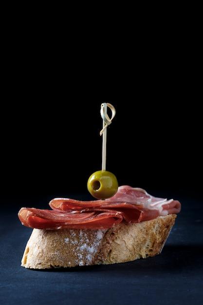 イベリコ生ハムと暗い背景にオリーブの串焼き Premium写真
