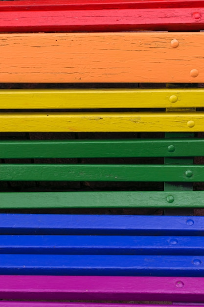 プライドデーのコンセプトの背景。虹色に塗られたベンチからの木 Premium写真