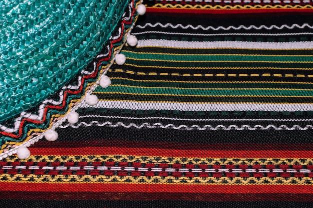 シンコデマヨの背景。メキシコの帽子と剥かれた毛布 Premium写真