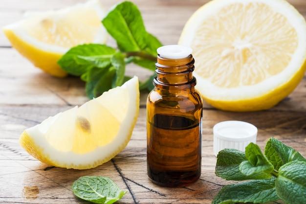 ボトルのエッセンシャルレモンオイル、木製の背景に新鮮なフルーツスライス。天然の香り Premium写真