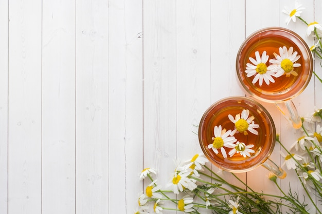 木製の背景にお茶とカモミールの花のカップ Premium写真