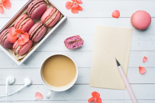 一杯のコーヒー、マカロンクッキー、ボックス、花、フラットのノートブック Premium写真