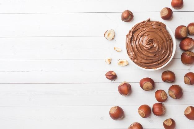 ヘーゼルナッツナッツと白い背景の上の皿にヌガーナッツチョコレート。 Premium写真