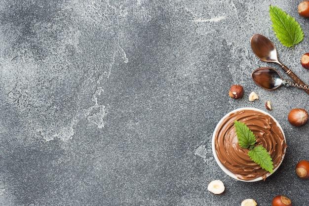 ヘーゼルナッツナッツと暗いコンクリートの背景にプレートのヌガーナッツチョコレート。 Premium写真