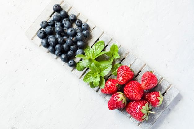 Свежие ягоды клубники черники мяты на деревянной подставке Premium Фотографии